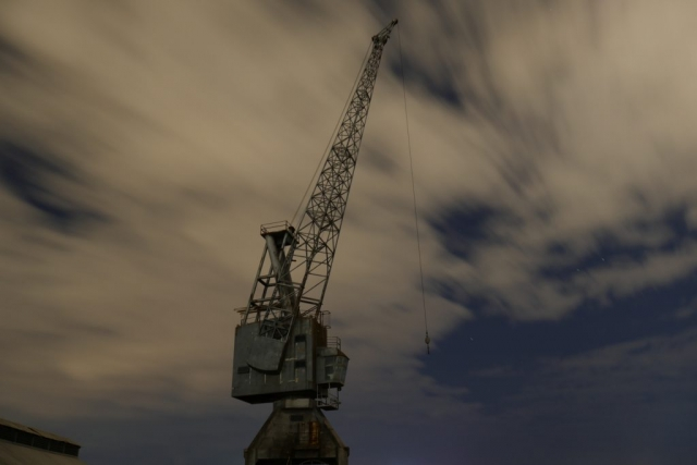 An old luffing wharf crane that on a cloudy night with patches of blue sky.  The clouds are blurry from the exposure length.  The crane is in focus and in the centre of the image.