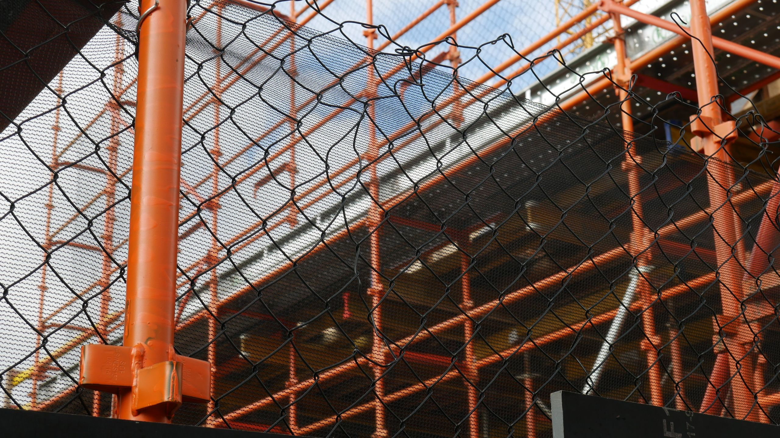 : In the foreground of the image there is black chain wire fence mesh with an orange standard on the left side of the image.  In the background the scaffolding runs diagonally back from the right of the image.  All the scaffolding is orange, the standards, the ledgers and the transoms.  In the top left corner, the sky is visible with lots of cloud cover.