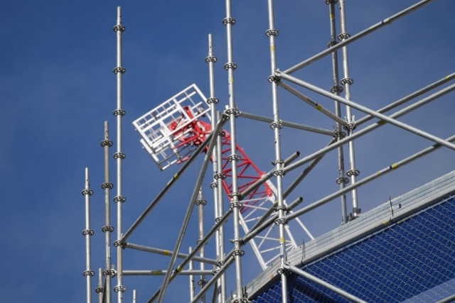 In the foreground the scaffolding is in a curved shape from the front right to the back of the image with a red and white top of a luffing tower crane behind the scaffold.
