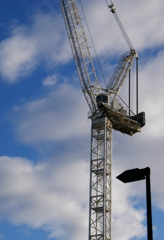 The white luffing tower crane is further back in the photo however is the focal point of the image.  In the foreground on the lower right corner has a black square street light with the light on.  The sky is mostly clouds with patches of blue sky.