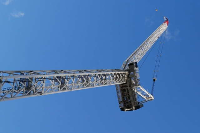 The white Liebherr 542 HC-L luffing tower carne is hozinotial in the photo.The mast of the tower crane comes into the centre on the left side with the plant deck on the right side of the image.The jib in the image is angled towards the top of the image.  The sky is blue in the photo with out any clouds.