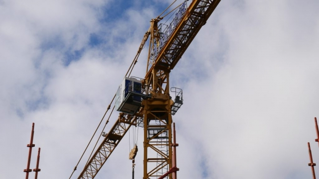The yellow fixed jib tower crane is in the centre of the photo.  The mast comes from the bottom centre of the image and the jib and plant deck go diagonally across the top of the image.  In the foreground at the bottom left and bottom right are four orange scaffolding standards.  The sky is cloudy with small amounts of blue sky.