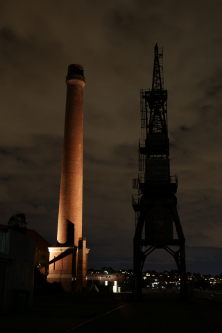The track luffing wharf crane is on the left side as a silhouette and the brick chimley has lights shining up from the base.  The photo has been taking of a night time and the clouds in the sky are blurring from the long exposure.