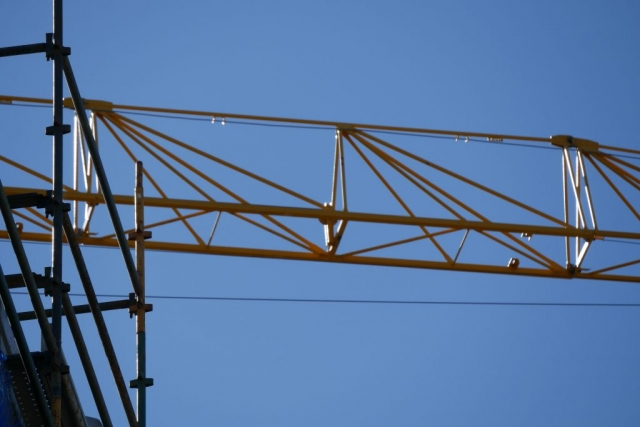 On the left of the image is a silhouette of a scaffold where the standers ledgers and transoms are visible.  Across the top of the image can be soon the fixed jib of a yellow tower crane.
