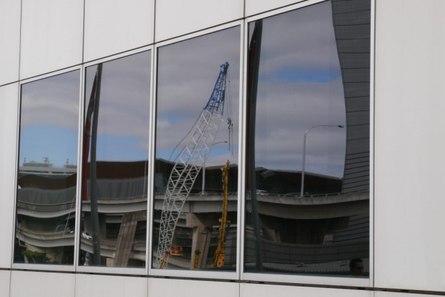 The image is a reflection in a window of a building.  The window is in the centre with four glass panels surrounded by grey wall panelling.  In the window glass, there is a reflection of the road bridges in the background in all four window panes.  In the third from the left window pane is a white and blue lattice boom crane and a yellow piling rig.