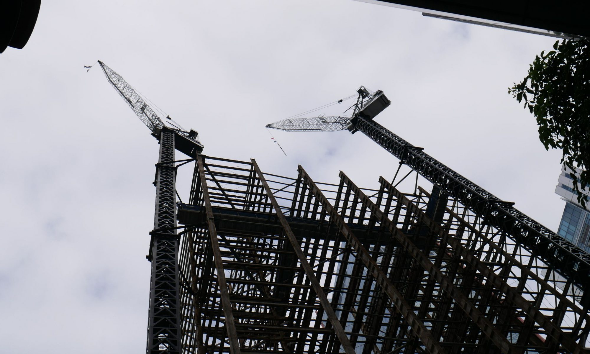 Pro Build Greenland Centre building steel structure looking up from the street with two tower cranes